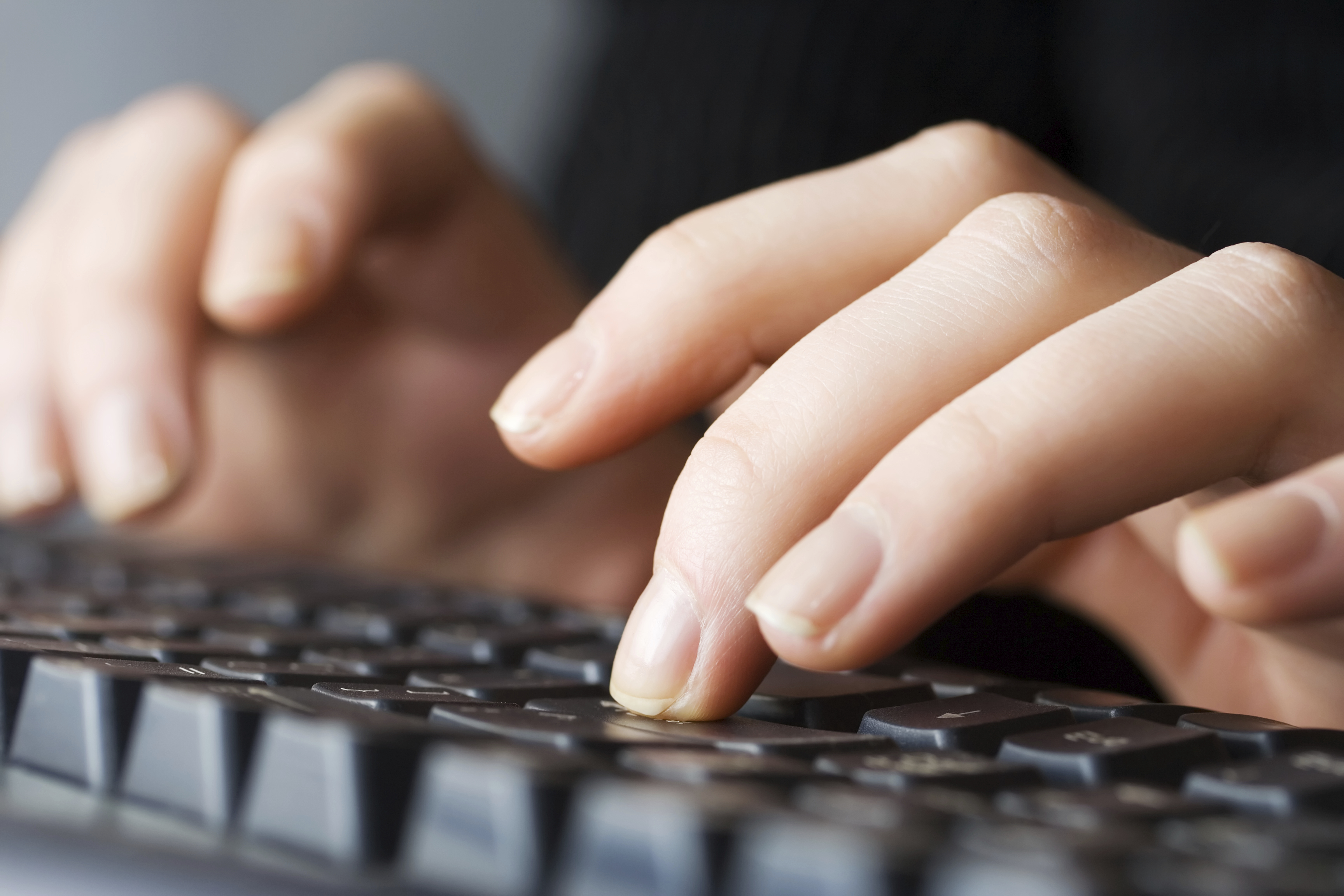 Close up of a female hands typing on keyboard.